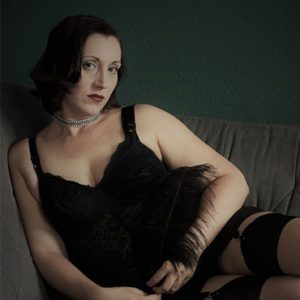 Lydia verführerisch auf dem Sofa mit Glitzer-Halsband und schwarzer Feder