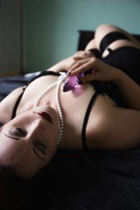 Versuchung Lydia mit Perlenkette, auf dem Bett liegend mit Glasdildo