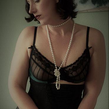 Lydia in schwarzen Dessous mit geknoteter Perlenkette