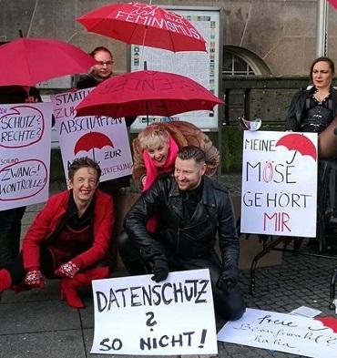 Mitglieder des BesD mit roten Schirmen und Plakaten bei einer Demo gegen das ProstSchG