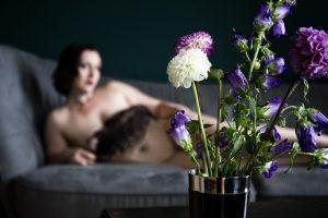 Lydia liegt nackt auf einem Sofa. Die intimen Stellen werden von einer schwarzen Feder und Blumen im Vordergrund verdeckt.