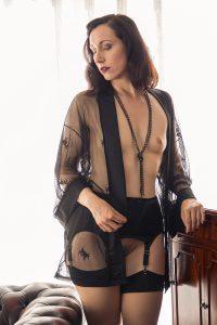 Versuchung Lydia sinnlich mit offenem Spitzen-Morgenmantel, der eine Brust erblicken lässt.