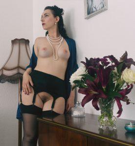 Lydia lehnt sich mit der linken Schulter an eine Wand, hinter ihr eine altmodische Stehlampe, vor ihr ein Schrank mit einem Blumenstrauß darauf. Sie trägt einen schwarzen Strumpfgürtel, schwarze Strümpfe, eine Perlenkette in vier Reihen und einen blau-grünen Satin-Morgenmantel, der ihr offen über die rechte Schulter fällt.