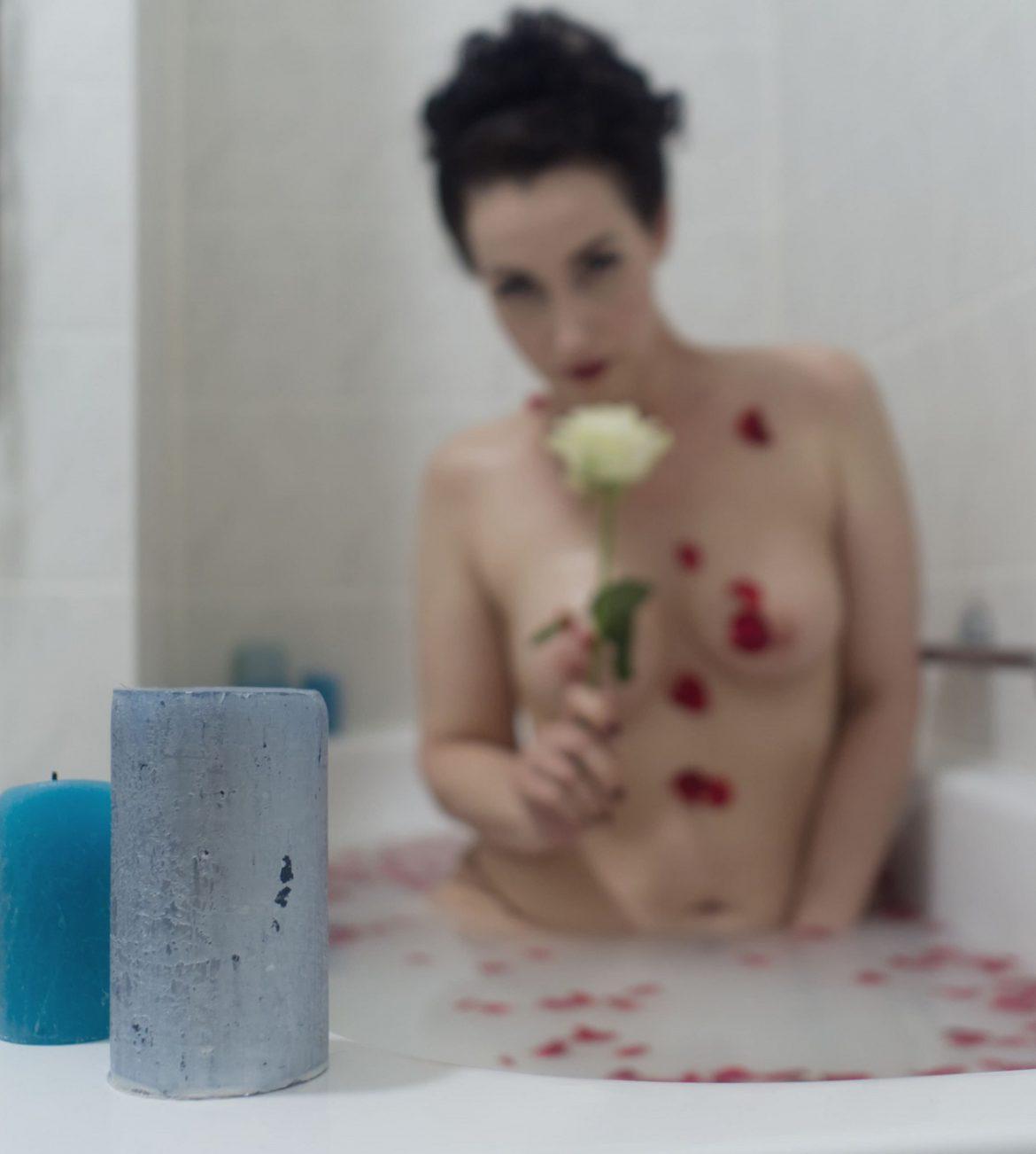 Lydia kniet in der Badewanne in milchigem Wasser, in welchem rote Rosenblütenblätter schwimmen. Sie ist nur verschwommen zu erkennen, blaue Kerzen im Vordergrund sind scharf. Die Blütenblätter haften auch an ihrem nackten Körper. In der rechten Hand hält sie eine weiße Rose und schaut darüber hinweg in die Kamera.