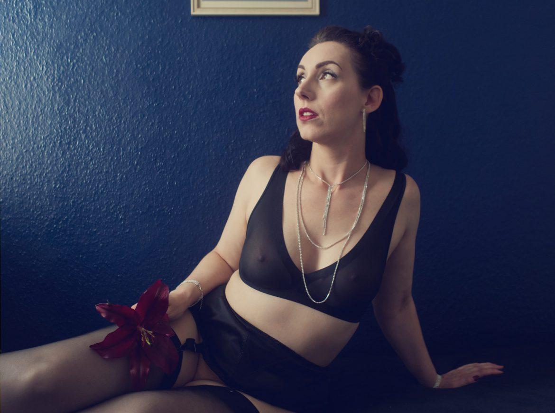 Lydia sitzt mit seitlich ausgestreckten Beinen, in schwarzen Dessous bekleidet, auf dem Bett, hinter ihr eine dunkelblaue Wand. Sie stützt sich auf ihren linken Arm und hat so den Oberkörper aufgerichtet. In der rechten Hand hält sie eine dunkelviolette Lilie. Sie schaut nachdenklich nach rechts.