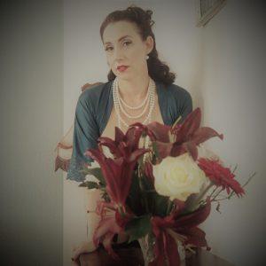 Lydia stützt sich auf einen kleinen Schrank, auf dem direkt vor ihr ein üppiger Blumenstrauß steht. Sie trägt eine vierreihige, weiße Perlenkette und schaut direkt in die Kamera.